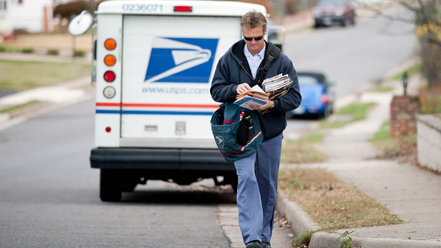 PHOTO: U.S. Postal Service city letter carrier Roy Sipe delivers mail to homes in Fairfax, Virginia, U.S., Nov. 30, 2011.