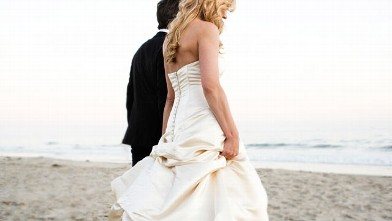 PHOTO: Bride and groom walking on beach