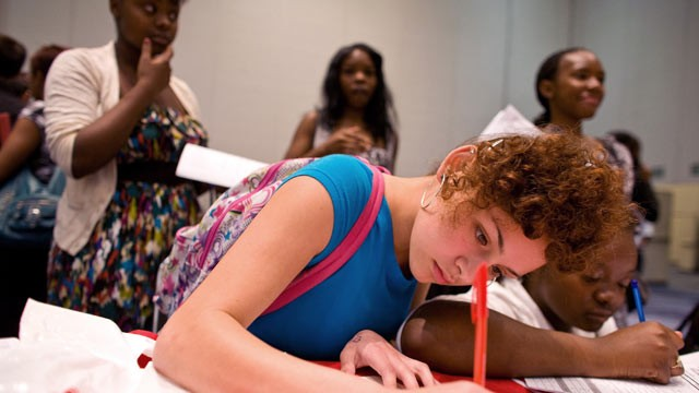 PHOTO: Jhada Thomas, 15, right, Alexis Lucero, 15, left, fill out job applications for Red Mango Inc. during The Summer Youth Jobs & Training Expo 2012 at the Colorado Convention Center in Denver, Colorado, U.S., on May 18, 2012.