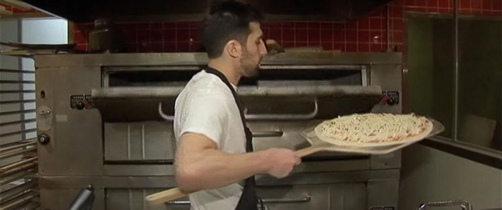 PHOTO: Owner Mason Wartman makes a pizza at Rosa's Fresh Pizza in Philadelphia. Patrons can buy a slice or two of pizza for the less fortunate.