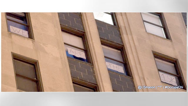 "PHOTO: A sign posted briefly in the windows of the Chicago Board of Trade and just as hastily taken down, visible to protesters in the street, declared, ""We Are The 1%."""