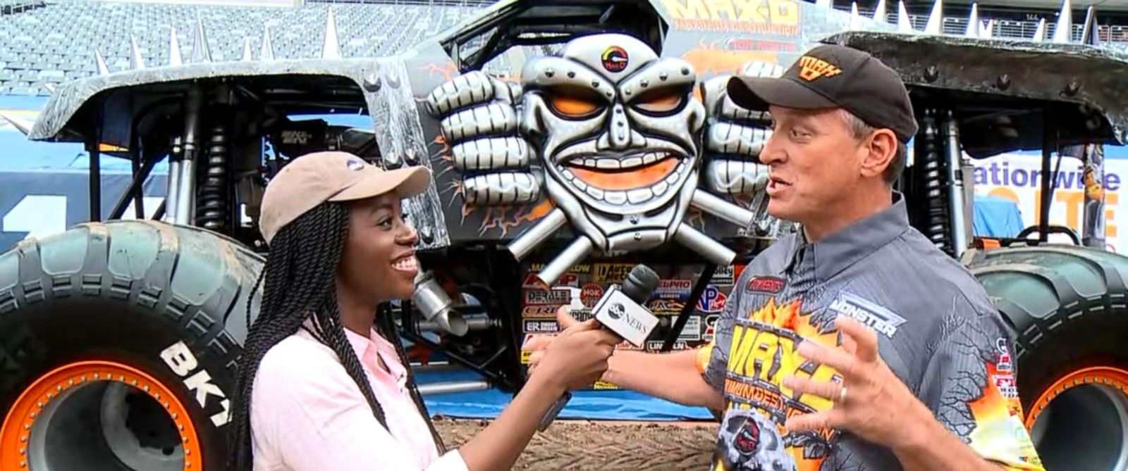 PHOTO: Nicole Phillip speaks with Monster Jam driver, Tom Meents in front of his car Max-D at a preview show for the event.