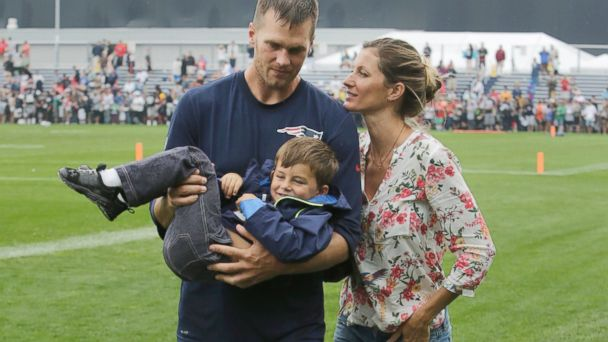 PHOTO: New England Patriots quarterback Tom Brady carries his son Benjamin with his wife Gisele Bundchen at right after a joint workout at NFL football training camp, in Foxborough, Mass., Aug. 13, 2013.