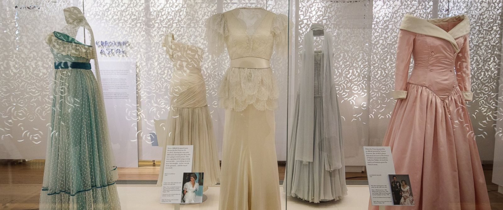 PHOTO: A 1990 Bruce Oldfield cream satin dress and a 1987 Catherine Walker pink satin evening gown (R) worn by princess Diana for an official portrait in 1987 at a press preview at Kensington Palace, on Feb. 22, 2017 in London.