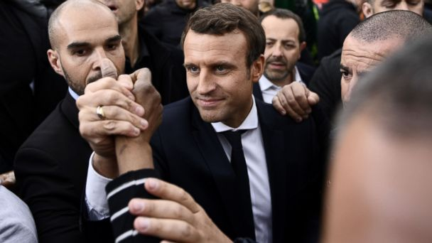 PHOTO: This file photo taken on April 27, 2017 in Sarcelles, north of Paris shows French presidential election candidate for the En Marche ! movement Emmanuel Macron (C) meeting with youth during a campaign visit.