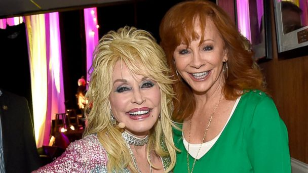 PHOTO: Reba McEntire visits Dolly Parton backstage during Dolly Parton: Pure & Simple Benefiting The Opry Trust Fund at Ryman Auditorium, Aug. 1, 2015, in Nashville, Tennessee.