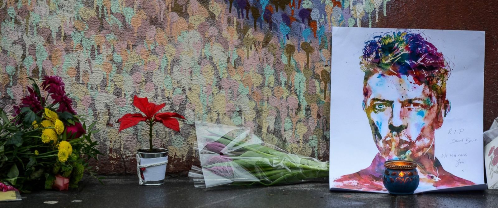 PHOTO: Floral tributes are left beneath a mural of British singer David Bowie, following the announcement of Bowies death, in Brixton, London, Jan. 11, 2016.