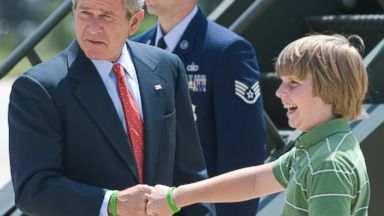 PHOTO: George W. Bush bumps fists with USA Freedom Corp volunteer Robbie Powell, 12, after arriving on Air Force One at Adams Field in Little Rock, Arkansas, July 2008.