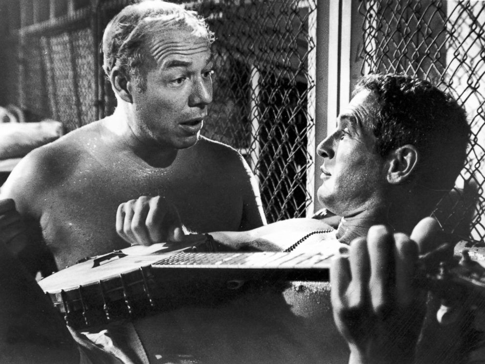 PHOTO: Paul Newman, playing a banjo, and George Kennedy talk in a still from the film Cool Hand Luke.