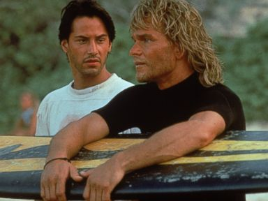 PHOTO: Actor Keanu Reeves and Patrick Swayze stand on a beach during the filming of the action movie Point Break in 1991.