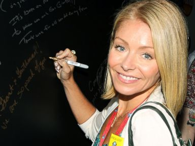 PHOTO: Kelly Ripa signs the Johnnie Walker Keep Walking Wall at Michael Strahans Hall of Fame Induction party in Canton, Ohio, Aug. 2, 2014.