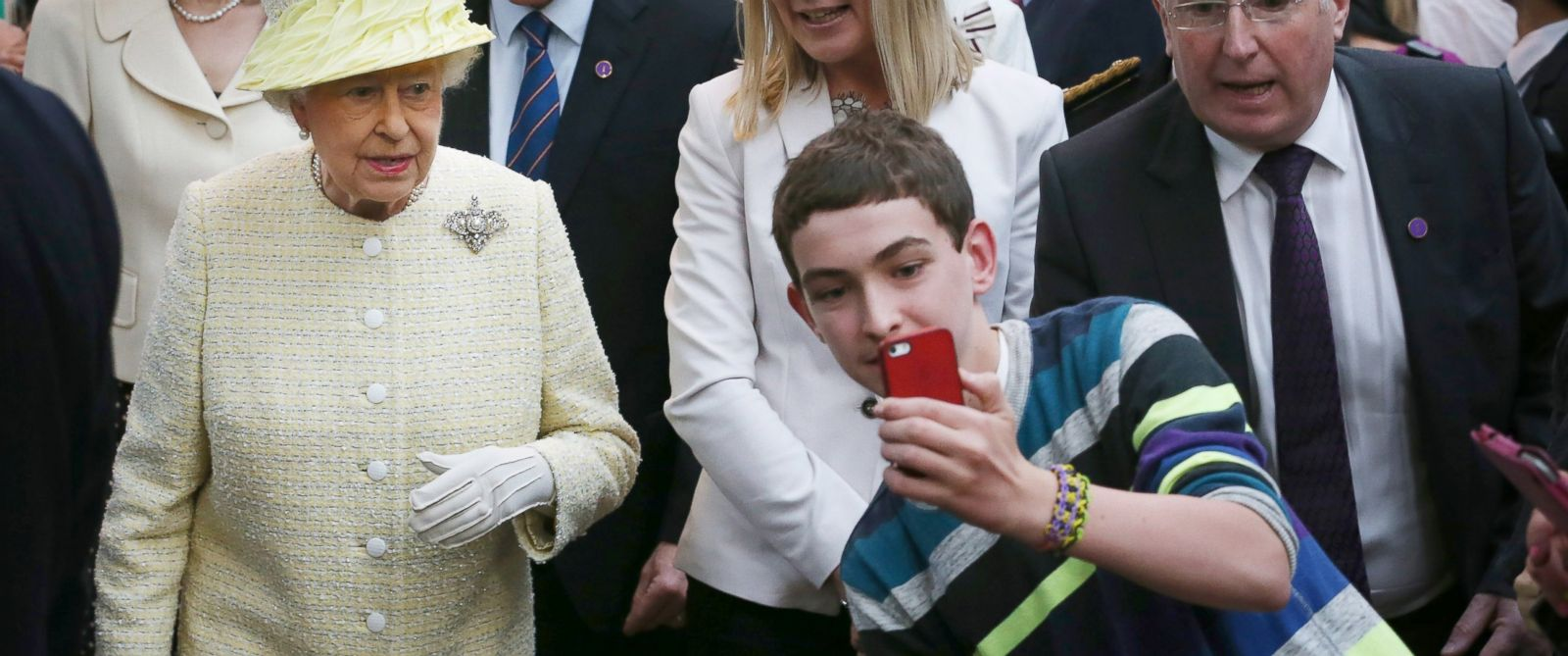 PHOTO: A teenager tries to take a selfie in front of Queen Elizabeth II during a walk around St. Georges Market in Belfast, Northern Ireland on June 24, 2014.