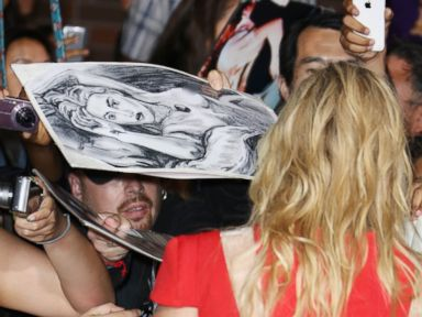 PHOTO: Kate Winslet signs autographs as a fan holds a naked drawing of Winslet from Titanic
