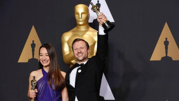 PHOTO: Orlando von Einsiedel and Joanna Natasegara hold their Oscars for Best Documentary Short Subject for