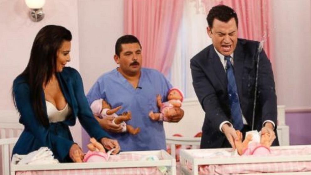 """PHOTO: Kim Kardashian and Jimmy Kimmel change diapers in a contest on """"Jimmy Kimmel Live,"""" Aug. 4, 2014."""