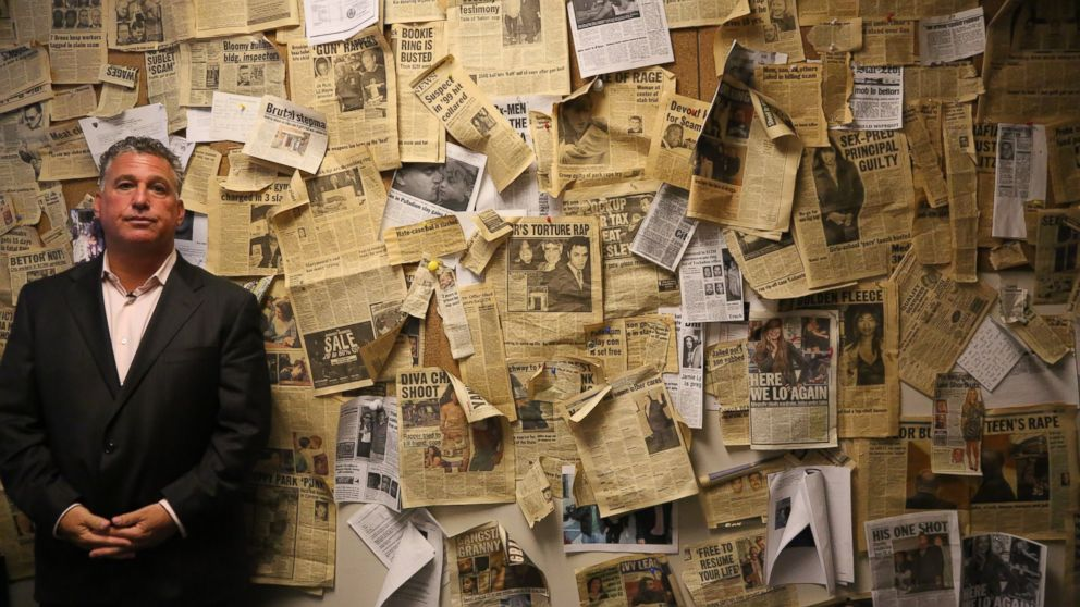 PHOTO: Ira Judelson, bail bondsman to the stars, stands in front of his wall of newspaper clippings from his high-profile cases at his office in New York City.