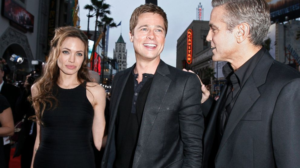 "PHOTO: Angelina Jolie looks on as Brad Pitt and George Clooney pose at the premiere of ""Oceans Thirteen"" in Los Angeles, on June 5, 2007."