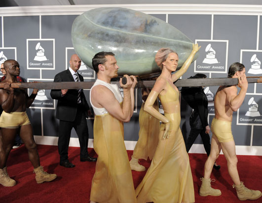"Lady Gaga, the singer known for her outrageous outfits, arrived at the Grammy Awards concealed in an egg. ""She is in an embryonic state and won't be born until the performance,"" a member of her entourage told Ryan Seacrest on ""E!"""
