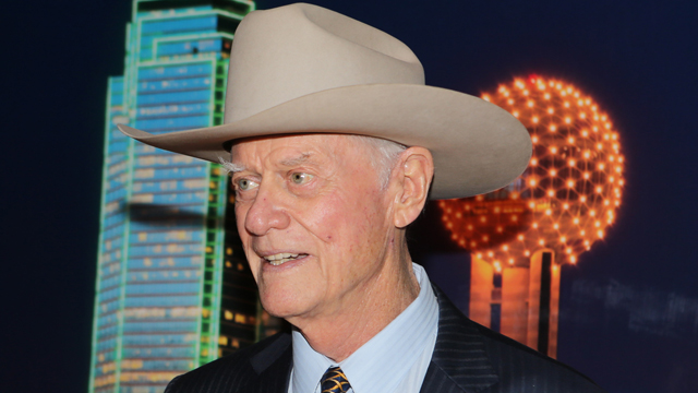 "PHOTO: American actor, director and producer, Larry Hagman, best known for his role as ""J.R. Ewing"" from the TV series Dallas poses for a photo in front of a backdrop with an image of downtown Dallas."