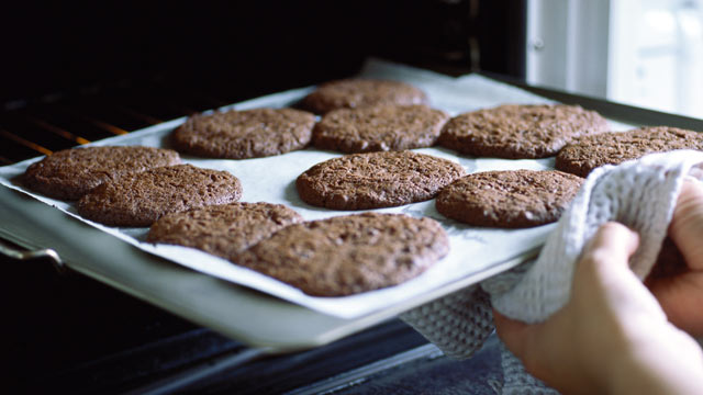 PHOTO: A woman takes a sheet of cookies out of the oven.