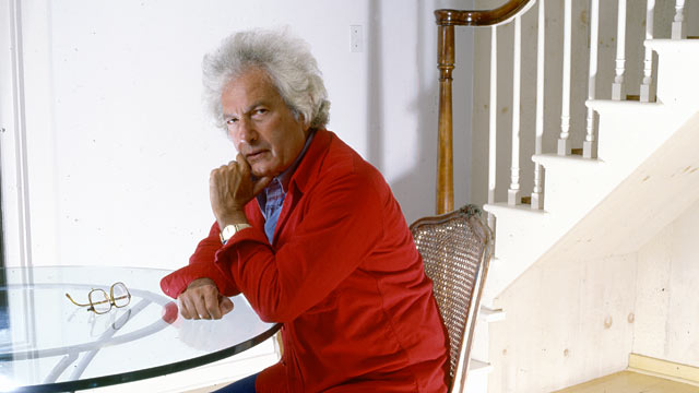 PHOTO: Portrait of American author Joseph Heller (1923 - 1999) as he sits at a glass-topped table near a staircase in his Long Island home, New York, 1985.