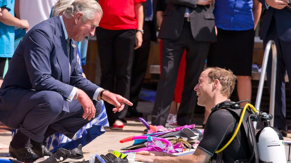 PHOTO: Britains Prince Charles, Prince of Wales speaks to his son Prince William, Duke of Cambridge as he scuba dives with British Sub-Aqua Club members at a swimming pool on July 9, 2014 in London, England.