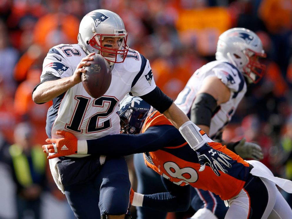 PHOTO: Tom Brady of the New England Patriots tries to evade a tackle by Von Miller of the Denver Broncos in the first half in the AFC Championship game at Sports Authority Field at Mile High on Jan. 24, 2016 in Denver, Colo.