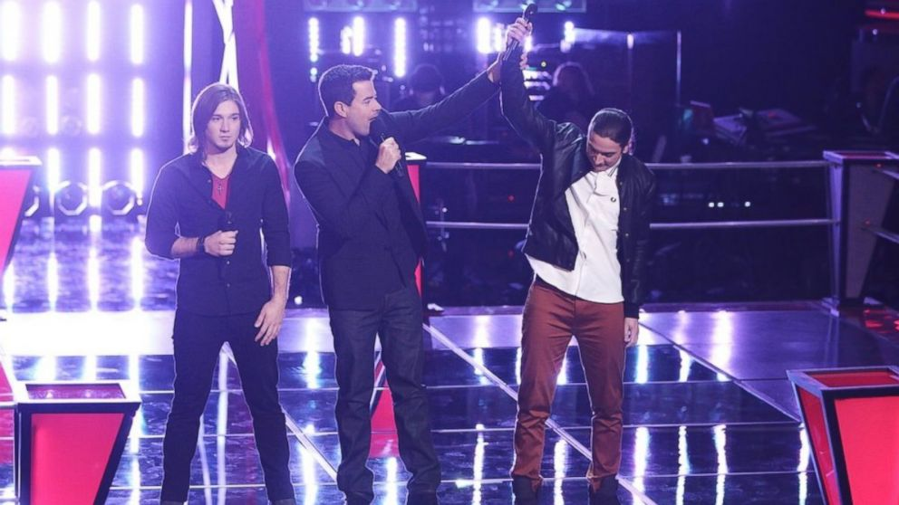 Contestants Morgan Wallen, left, and Stevie Jo, right, are seen with host Carson Daly during an episode of The Voice, April 1. 2014.