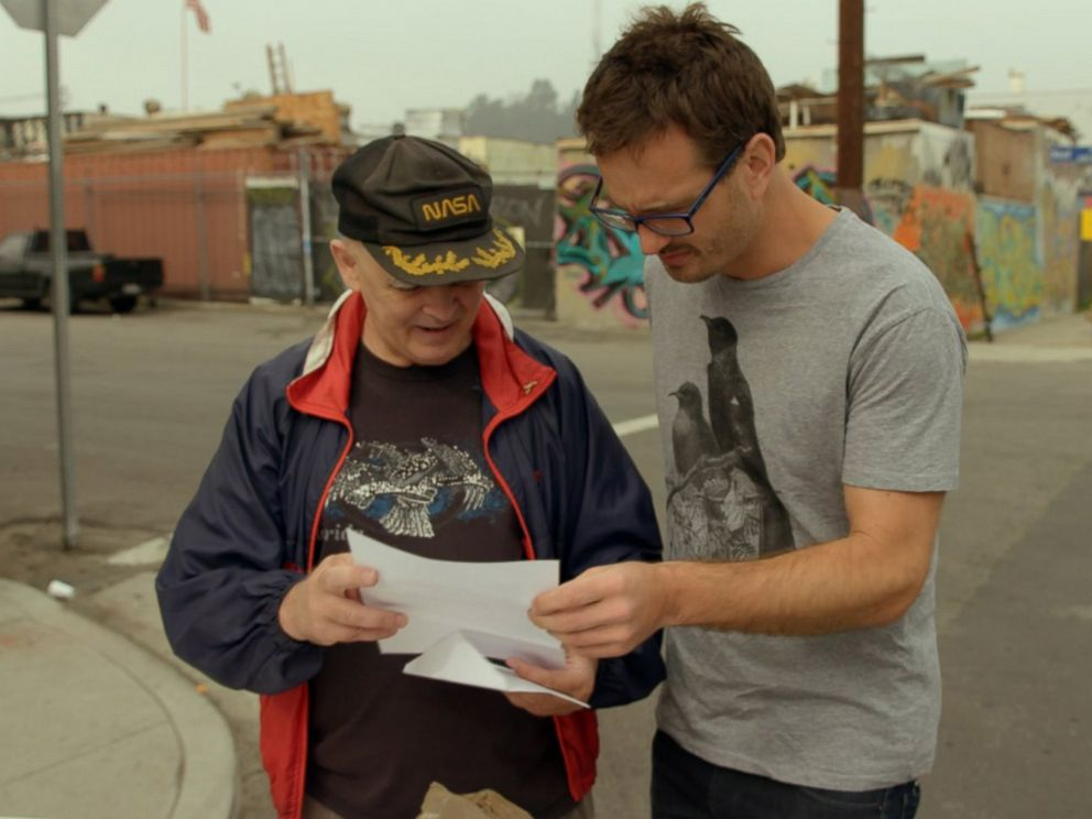 PHOTO: David Farrier, right, looks at documents in the film, Tickled.
