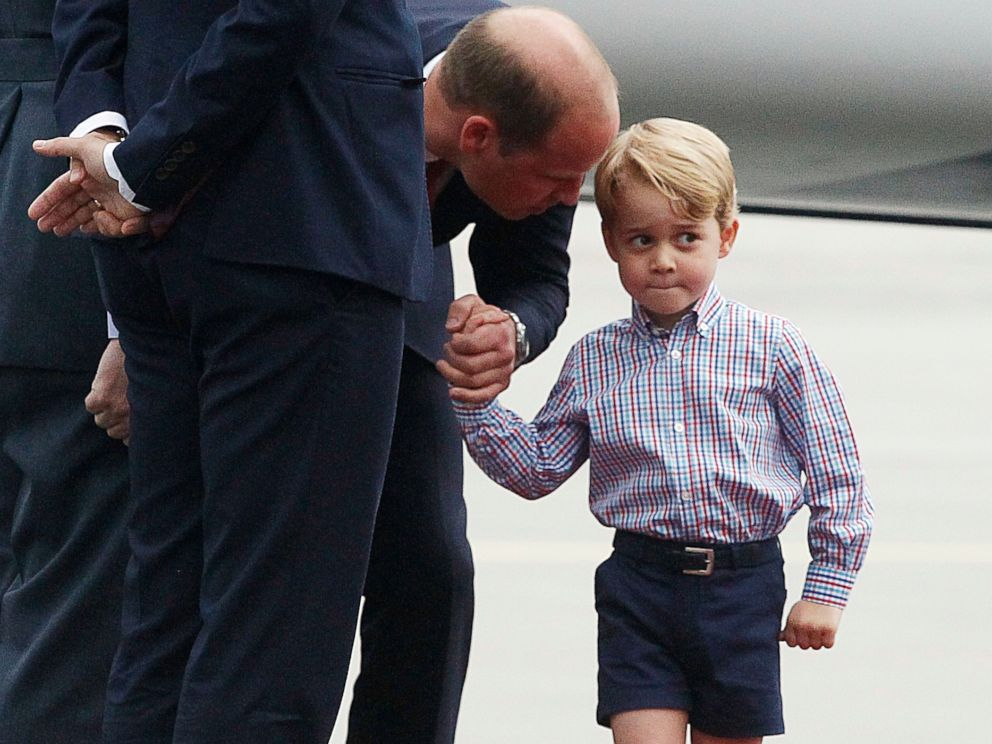 PHOTO: Britains Prince William, left, holds the hand of his son Prince George on arrival at the airport, in Warsaw, Poland, July 17, 2017.