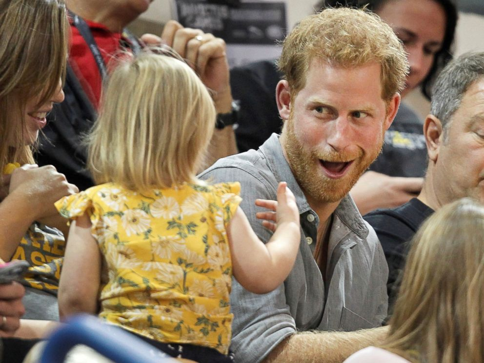 PHOTO: Britains Prince Harry, patron of the Invictus Games Foundation, shares popcorn with a child while attending the Sitting Volleyball competition at the games in Toronto, Sept. 27, 2017.