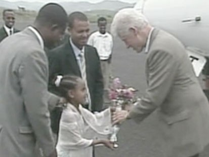 Little girl handing Bill Clinton flowers