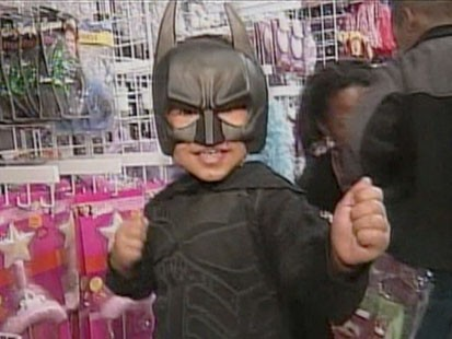 A picture of a little boy in a Batman costume.