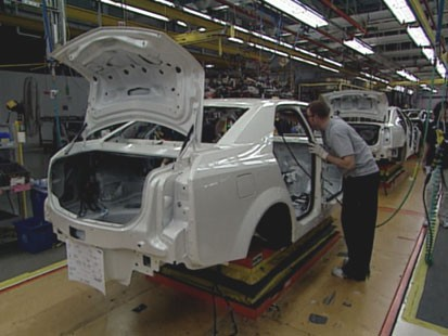 A picture of a car being made on an assembly line.