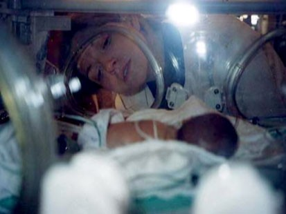 VIDEO: A woman looking at her premature baby in an incubator.