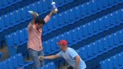 VIDEO: Video shows a fan make an incredible catch with his hands full.