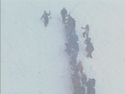 A picture of a search party walking through the snow.