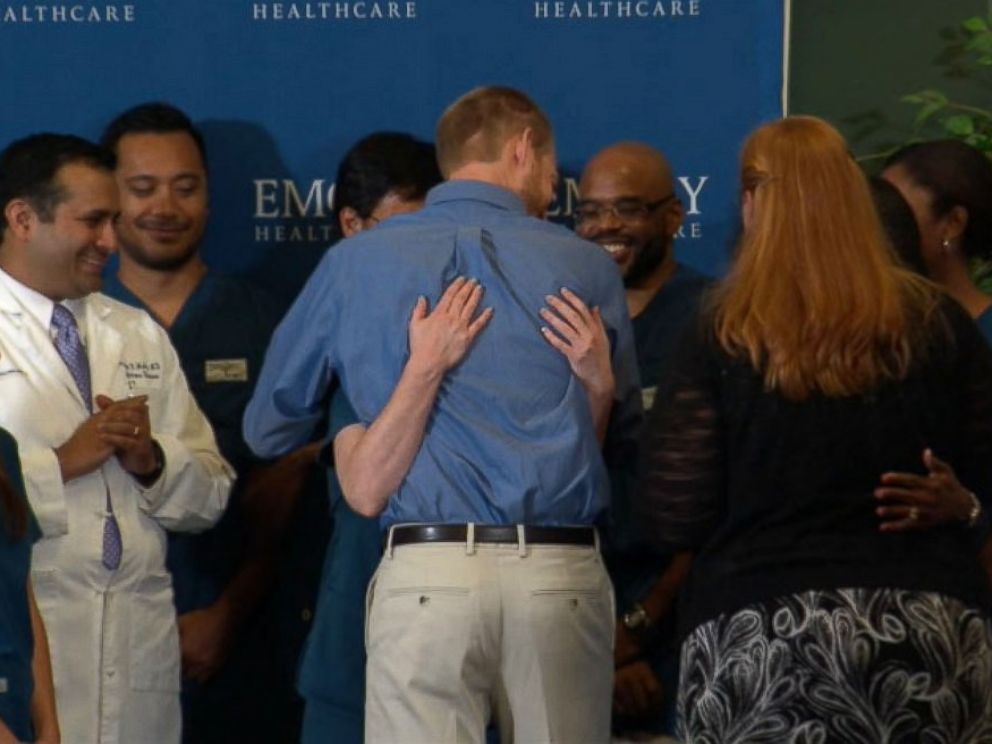 PHOTO: Dr. Kent Brantly hugs the staff at Emory Hospital after speaking at a press conference