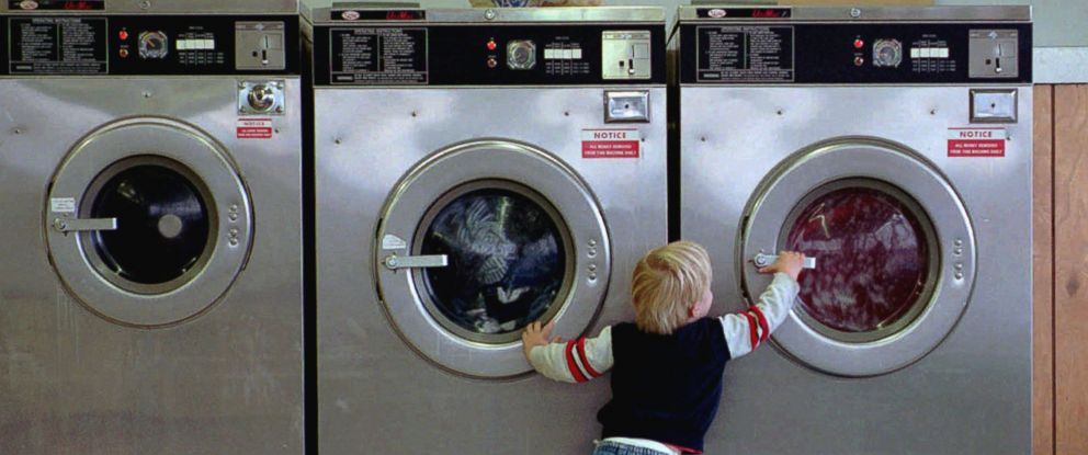 PHOTO: A young boy reaches for his familys laundry during the middle of the washing cycle at a laundromat in North Bend, Ore. The child always comes with his grandmother and his mother to help them with the laundry.