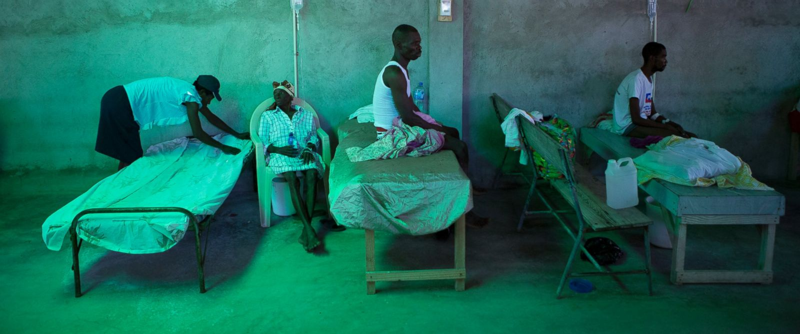PHOTO: The daughter of 84-year-old Armant Germain replaces the sheets on her bed, in the cholera ward at a hospital in Les Cayes Haiti, on Oct. 11, 2016.