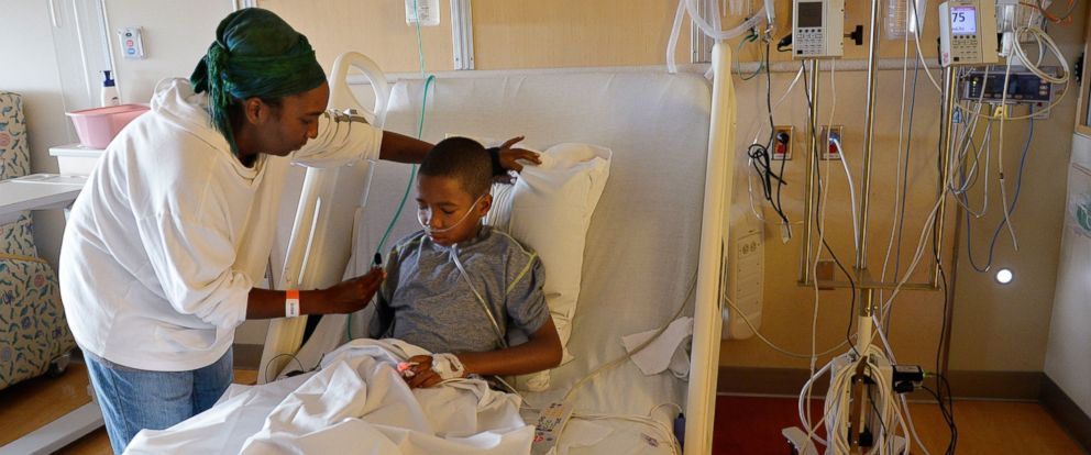 PHOTO: Melissa Lewis, of Denver, helps her son, Jayden Broadway, 9, as he coughs in his bed at the Childrens Hospital Colorado in Aurora, Colo., Sept. 8, 2014.