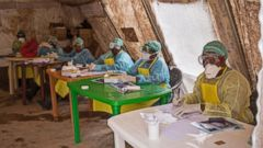 PHOTO: In this photo taken Saturday, Aug. 9, 2014, a health worker wearing protective clothing and equipment, await patients to screen against the deadly Ebola virus at the Kenema Government Hospital.