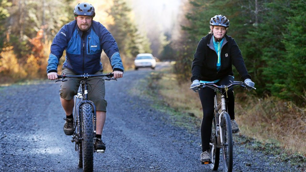 PHOTO: Nurse Kaci Hickox, right, and her boyfriend, Ted Wilbur are followed by a Maine State Trooper as they ride bikes on a trail near her home in Fort Kent, Maine, Oct. 30, 2014.