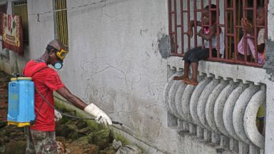 PHOTO: A man that was hired by the community sprays chemicals to try and prevent the spread of the Ebola virus, as local children look on, in Monrovia, Liberia, Aug. 29, 2014.
