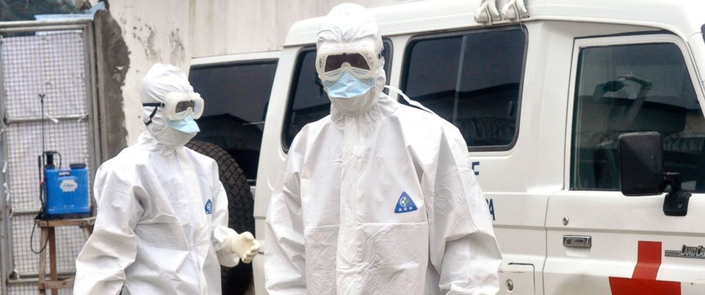 PHOTO: Health workers wearing protective gear wait to carry the body of a person suspected to have died from Ebola, in Monrovia, Liberia, Oct. 13, 2014.