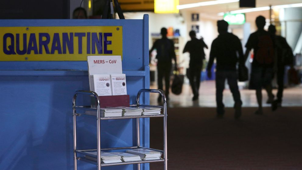 PHOTO: Passengers walk past the medical quarantine area showing information sheets for the Middle East respiratory syndrome coronavirus at the arrival section of Manilas International Airport in Paranaque, south of Manila, Wednesday, April 16, 2014.