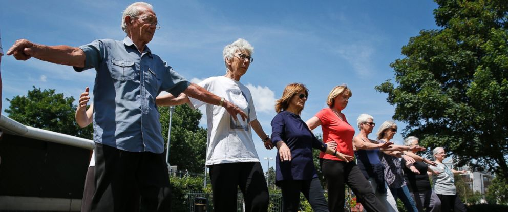 PHOTO: 85-year-old George Jackson, left, an army veteran and former boxer, 79-year-old Lara Thomson, 2nd left, and others participate at a parkour class for elderly people at a park in London, England on June 17, 2014.