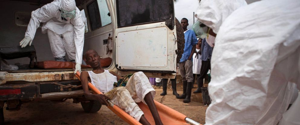 PHOTO: Healthcare workers load a man, center, onto a ambulance as he is suspected of suffering from the Ebola virus in Kenema, Sierra Leone, Sept. 24, 2014.