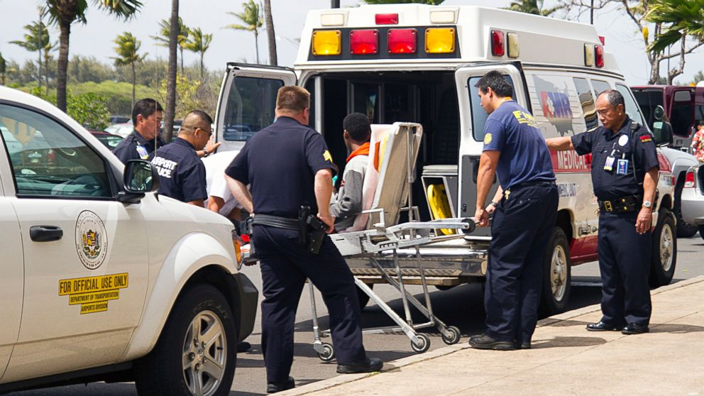 PHOTO: A 16-year-old boy, seen sitting on a stretcher center, who stowed away in the wheel well of a flight from San Jose, Calif., to Maui is loaded into an ambulance at Kahului Airport in Kahului, Maui, Hawaii, April, 20, 2014.