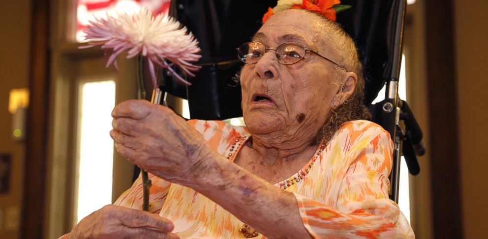 PHOTO: Gertrude Weaver holds a flower given to her a day before her 116th birthday, at Silver Oaks Health and Rehabilitation Center in Camden, Ark. on July 3, 2014.